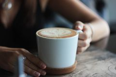 Grande tasse blanche avec le cappuccino dans des mains femelles, foyer sélectif images libres de droits