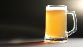 Grande tasse de bière fraîche de métier avec des bulles de mousse et d'air d'isolement au fond clair noir de studio banque de vidéos