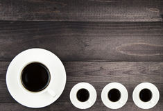 Grande tasse de café blanc et trois petites tasses Photos stock