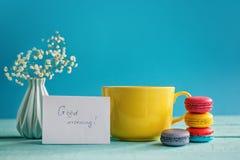 Grande tasse de thé avec la fleur et les macarons de wite avec le blanc sur le fond bleu Photo libre de droits