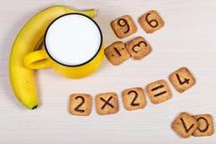 Grande tasse jaune de lait, de banane et de biscuits drôles avec des nombres sur le fond en bois clair Petit déjeuner sain pour u Image stock