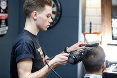 Grande tempo no barbeiro Homem farpado novo alegre que obtém o corte de cabelo pelo cabeleireiro ao sentar-se na cadeira no barbe Fotografia de Stock