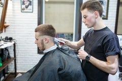 Grande tempo no barbeiro Homem farpado novo alegre que obtém o corte de cabelo pelo cabeleireiro ao sentar-se na cadeira no barbe Fotografia de Stock Royalty Free