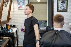 Grande tempo no barbeiro Homem farpado novo alegre que obtém o corte de cabelo pelo cabeleireiro ao sentar-se na cadeira no barbe Foto de Stock Royalty Free