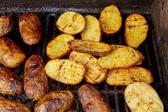 Grande tranche de pommes de terre de style du village sur le gril chaud de charbon de bois de BBQ Photographie stock libre de droits
