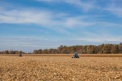 Grande trattore blu due che ara la terra dopo avere effettuato il raccolto del cereale su un soleggiato, chiaro, giorno di autunn Immagine Stock