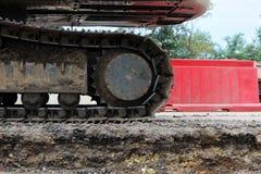 Grande trattore a cingoli dell'escavatore sulle recinzioni della plastica del fondo fotografia stock libera da diritti