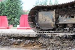 Grande trattore a cingoli dell'escavatore sulle recinzioni della plastica del fondo fotografie stock libere da diritti