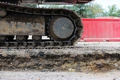 Grande trattore a cingoli dell'escavatore sulle recinzioni della plastica del fondo fotografie stock