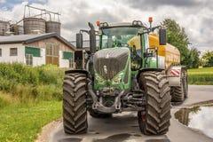 Grande trattore vigoroso con l'azienda agricola nei precedenti fotografia stock libera da diritti