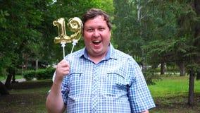 Grande uomo che tiene i palloni dorati che rendono il numero 19 all'aperto diciannovesimo partito di celebrazione di anniversario stock footage
