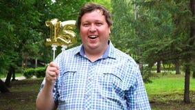 Grande uomo che tiene i palloni dorati che rendono il numero 15 all'aperto sedicesimo partito di celebrazione di anniversario video d archivio