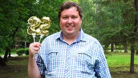 Grande uomo che tiene i palloni dorati che rendono il numero 22 all'aperto 22th partito di celebrazione di anniversario archivi video