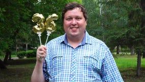 Grande uomo che tiene i palloni dorati che rendono il numero 36 all'aperto trentaseiesimo partito di celebrazione di anniversario video d archivio