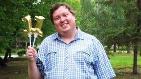Grande uomo che tiene i palloni dorati che rendono il numero 11 all'aperto undicesimo partito di celebrazione di anniversario archivi video