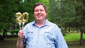 Grande uomo che tiene i palloni dorati che rendono il numero 20 all'aperto ventesimo partito di celebrazione di anniversario archivi video