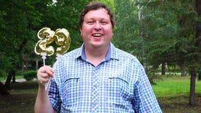 Grande uomo che tiene i palloni dorati che rendono il numero 29 all'aperto ventinovesimo partito di celebrazione di anniversario stock footage