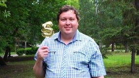 Grande uomo che tiene pallone dorato che rende il numero 5 all'aperto Partito di celebrazione di quinto anniversario archivi video