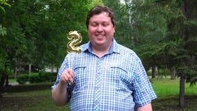 Grande uomo che tiene pallone dorato che rende il numero 2 all'aperto 2th partito di celebrazione di anniversario stock footage