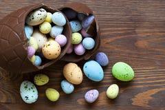 Grande uovo di Pasqua del cioccolato in pieno di piccola caramella Fotografia Stock Libera da Diritti