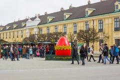Grande uovo rosso al mercato di Pasqua a Vienna e la gente che cammina intorno Fotografie Stock