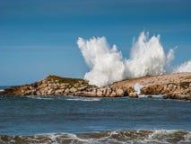 Grande vague au-dessus des roches Photo stock