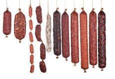 Grande variété de saucisses verticalement disposées de salami d'isolement Image libre de droits