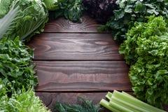 Grande variedade da carcaça da alface e dos verdes, em torno de uma tabela de madeira com um lugar para o texto foto de stock royalty free