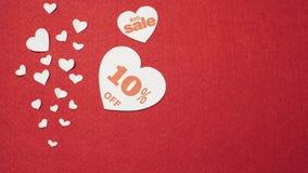 Grande vente au coeur blanc sur le fond rouge La main de l'homme ajoute 10 pour cent écrits sur le coeur banque de vidéos