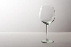 Grande vetro/vetro trasparente vuoto di vino che sta su un fondo grigio Fotografie Stock