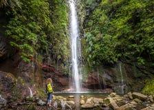 Grande viandante della donna e della cascata al levada 25 fontane in Rabacal, isola del Madera Fotografia Stock