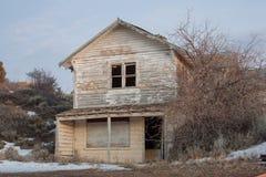 Grande vieille maison abandonnée entourée par les arbres nus d'hiver Photos libres de droits