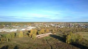 Grande villaggio aereo con il complesso del bestiame sotto cielo blu video d archivio