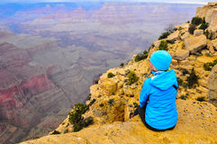 A grande vista. Mature woman sitting on the edge of the grand canyon enjoying a stormy sunset view Stock Photo