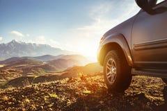 Grande voiture 4x4 contre le coucher du soleil et les montagnes Image libre de droits