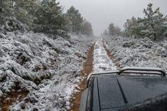 Grande voiture 4x4 sur la voie avec la neige Photographie stock