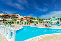 Grande vue de invitation des au sol coloniaux d'hôtel, de la belle piscine et des rétros bâtiments élégants sur le ciel bleu prof Images libres de droits