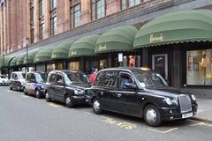 Grandes almacenes de Harrods de los taxis del negro de Londres Foto de archivo libre de regalías