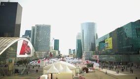 Grandes barracas no centro da cidade, rua justa, caminhada dos povos perto das construções de vidro modernas vídeos de arquivo