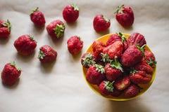 Grandes belles fraises rouges juteuses mûres à un arrière-plan jaune de cuvette et de métier Photo stock