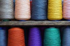 Grandes bobines multicolores de fil dans une rangée Traitements différés d'amorçage coloré images libres de droits