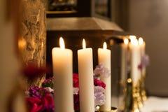 Grandes bougies brûlant dans l'église avec le fond brouillé image stock