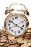 Grandes caras de oro del reloj de alarma en monedas Imagen de archivo libre de regalías