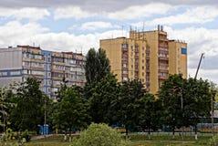 Grandes casas residenciais atrás das árvores verdes e grama na jarda Foto de Stock