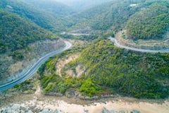 Grandes courbures de route d'océan par des collines image libre de droits