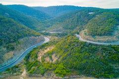 Grandes curvaturas da estrada do oceano através dos montes florestados foto de stock