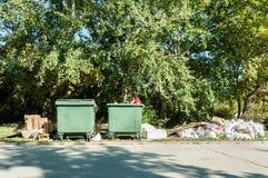 Grandes deux poubelles en plastique vertes de décharge complètement des ordures de débordement polluant le parc et la rue dans la photographie stock libre de droits
