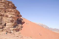 Grandes duna e povos vermelhos que escalam acima e correm para baixo no deserto de Wadi Rum foto de stock royalty free