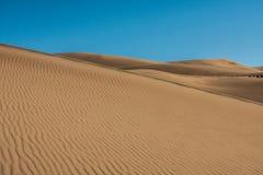 Grandes dunas de arena con el cielo brillante, azul Fotos de archivo libres de regalías