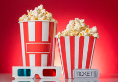 Grandes et petites boîtes à maïs éclaté, un billet aux films, verres 3d sur le rouge Images stock